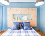 Dormitorio azul con cabecero de madera iluminado