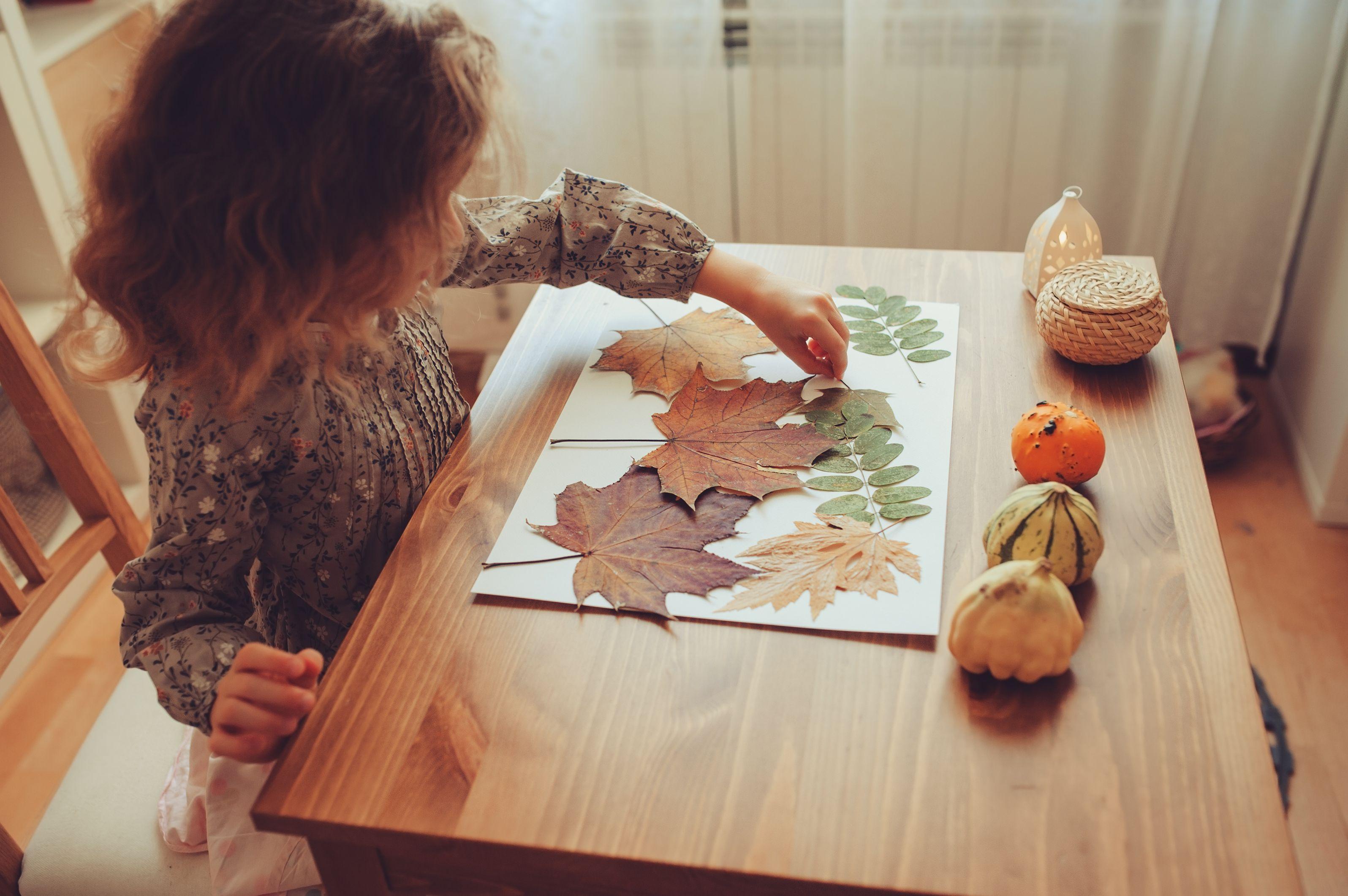 Niña haciendo un collage de hojas secas