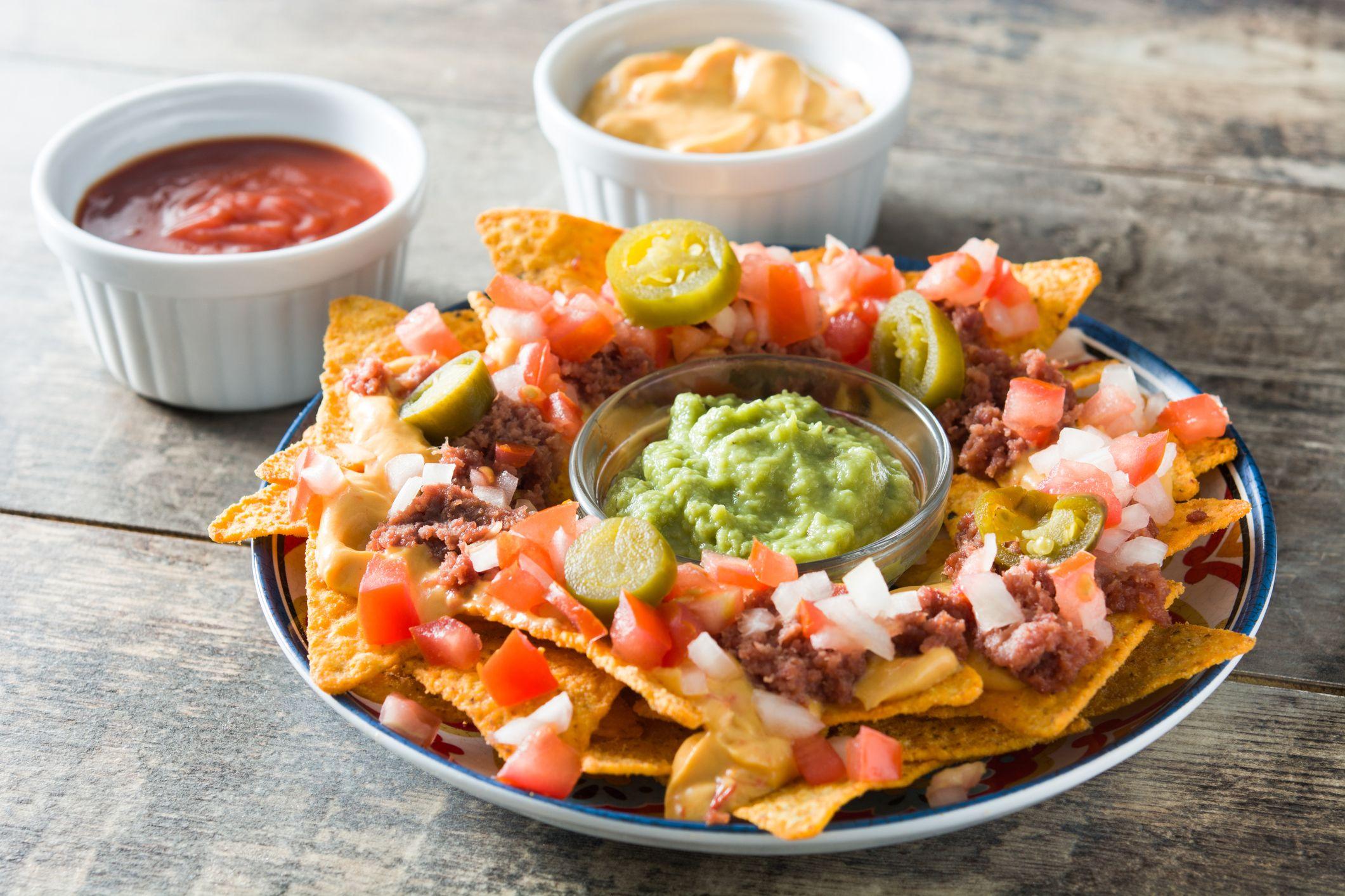 Totopos o nachos mexicanos acompañados de guacamole, frijoles o salsas para untar.