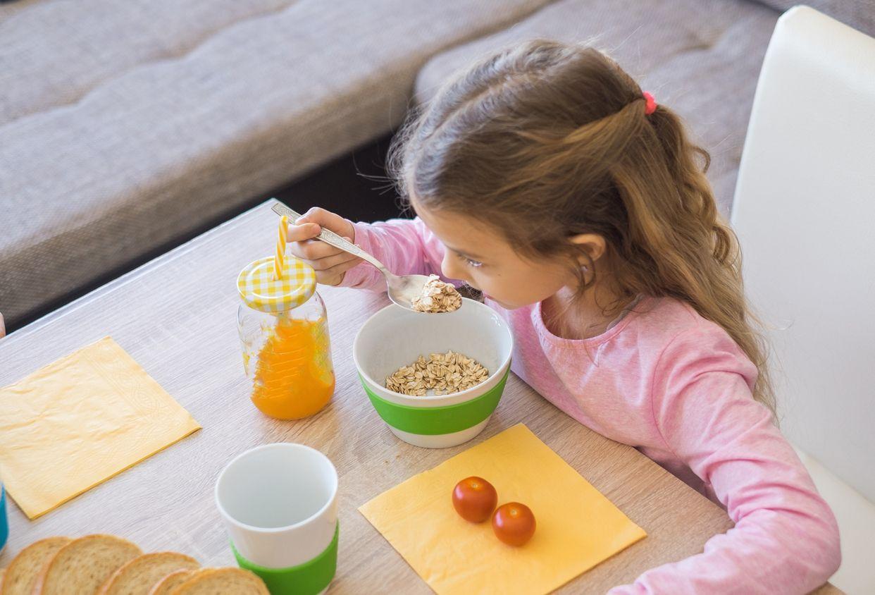 Niña desayunando cereales y zumo.