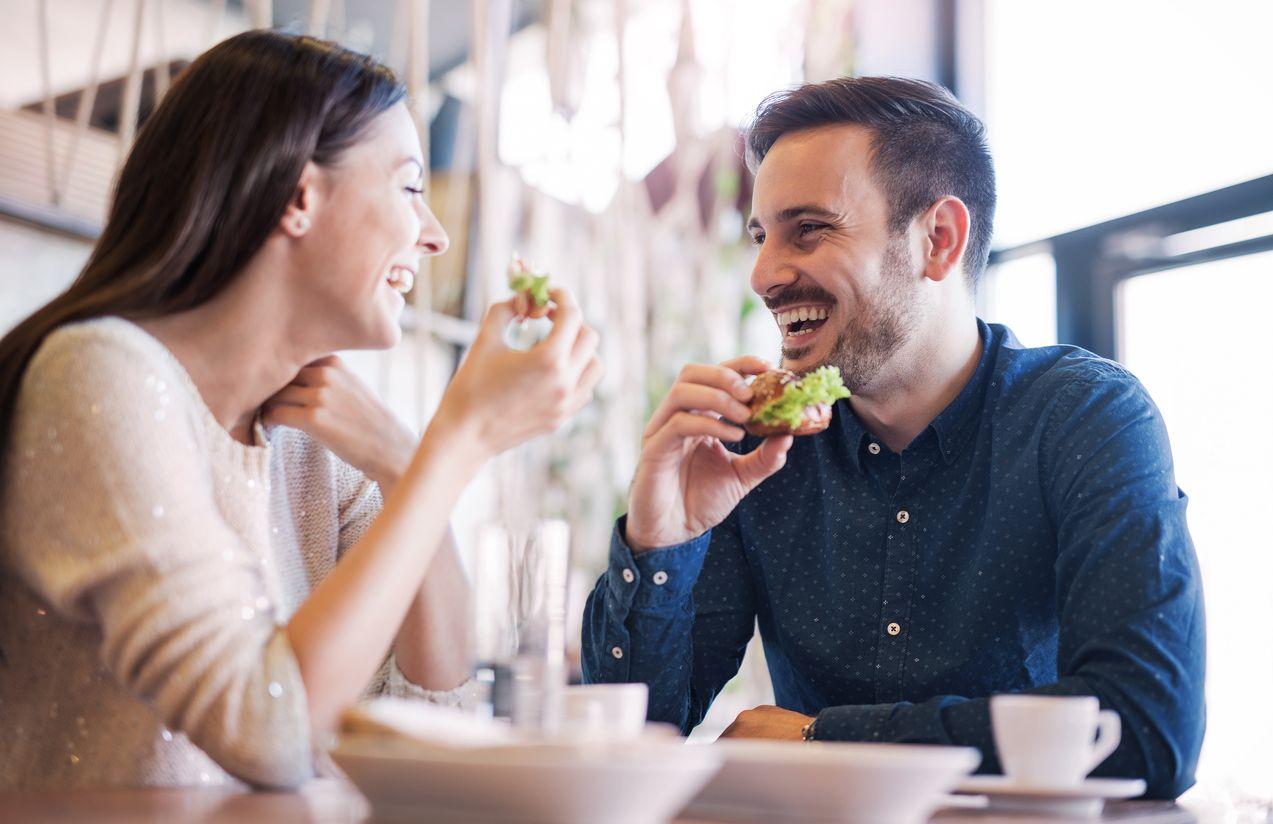 Pareja disfruta de una conversación agradable durante la comida.