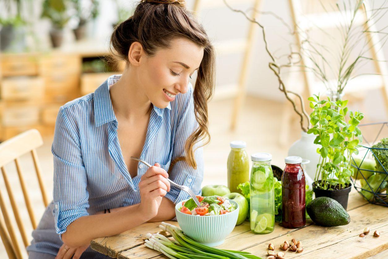 Mujer comiendo una ensalada saludable.