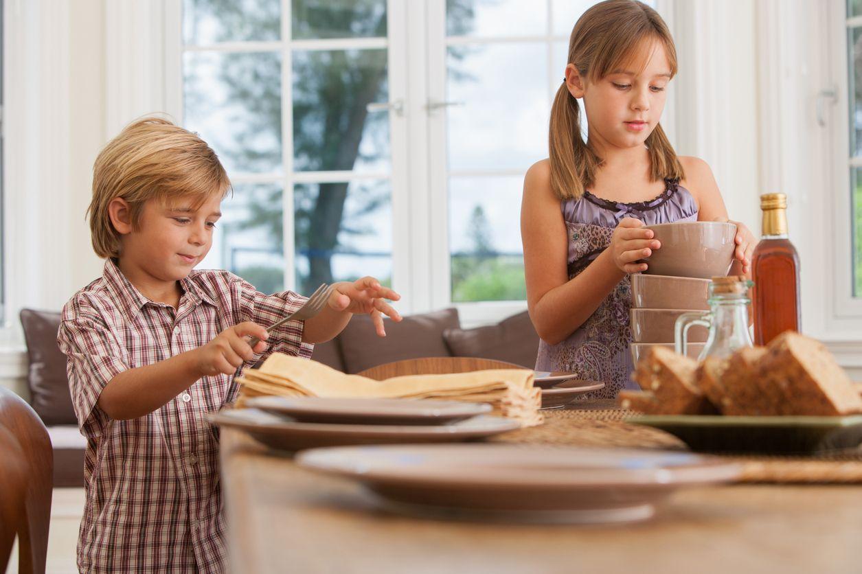 Niños poniendo la mesa antes de comer.