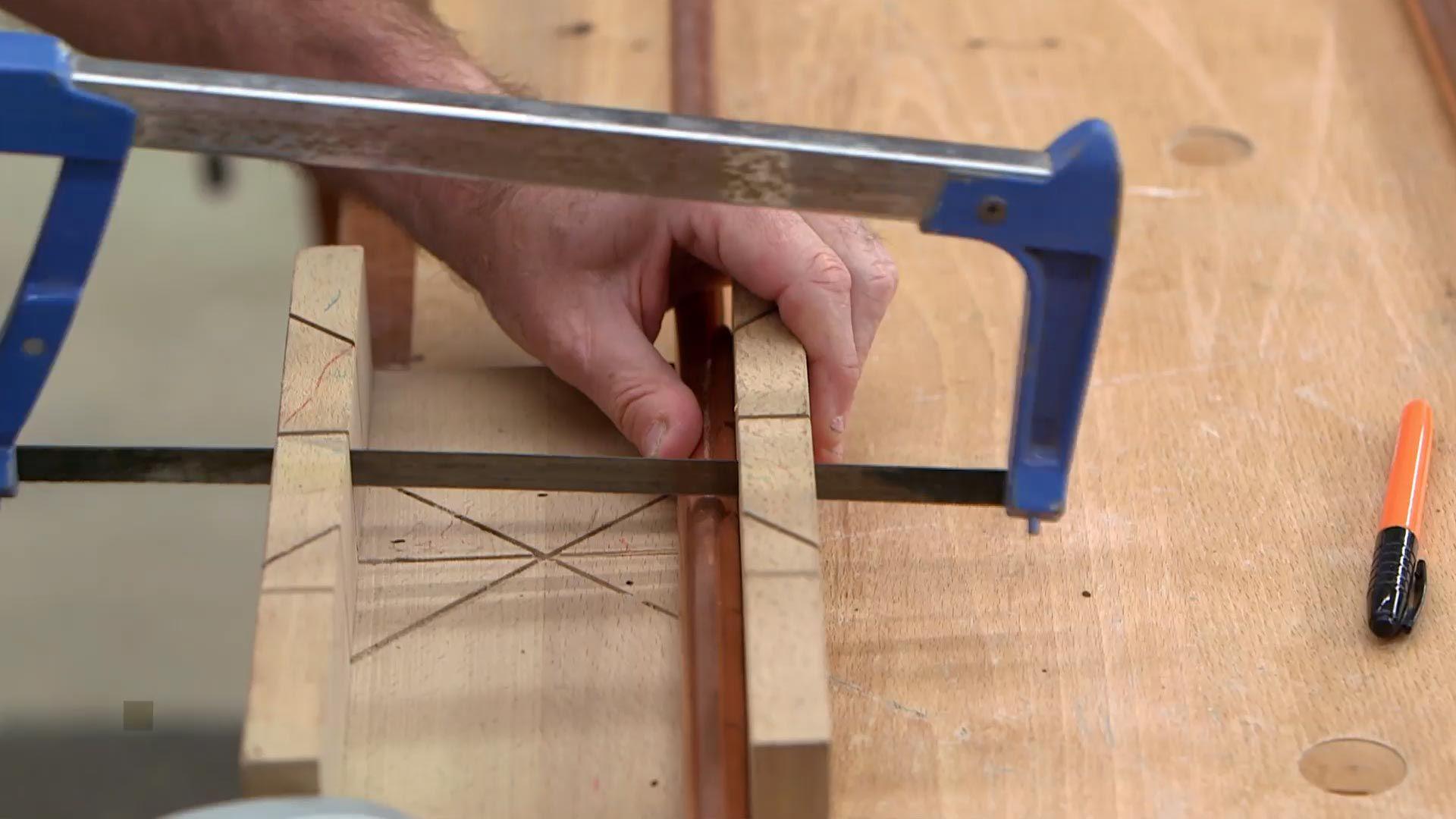 Cortar tubos de cobre con una sierra y una caja de ingletes