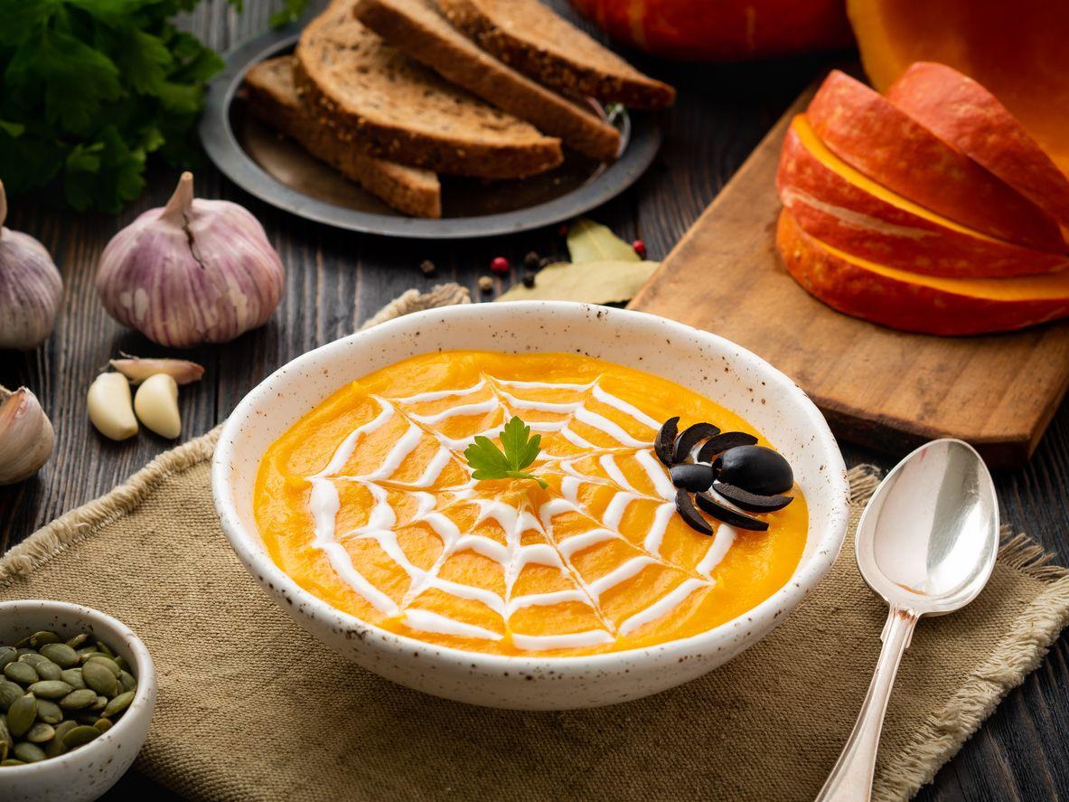 Crema de calabaza con tela de araña de queso fundido para Halloween.