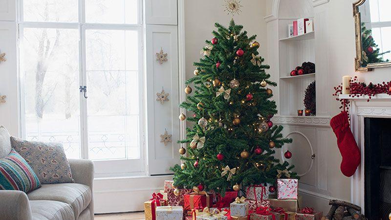 Árbol de Navidad clásico con adornos en tonos rojos y dorados.
