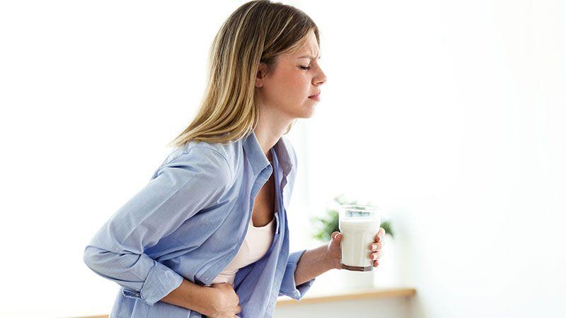 Chica con dolor de estómago sosteniendo un vaso de leche.