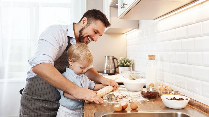 Niño pequeño amasando galletas con ayuda de su padre.