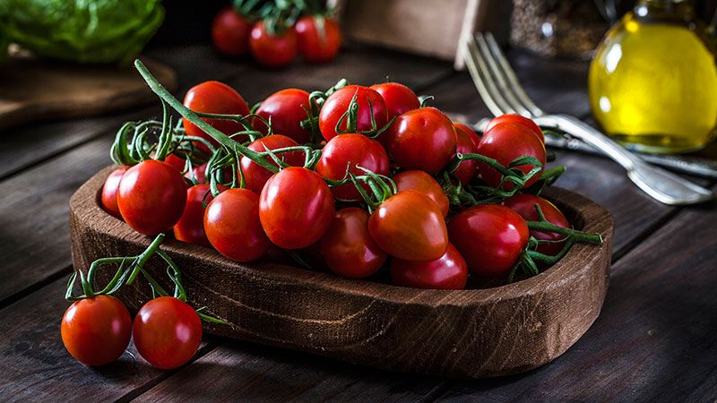 Tomate cherry orgánico en mesa de madera rústica