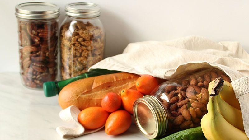 Frutos secos a granel en tarros de cristal y verduras en bolsa de tela reutilizable.