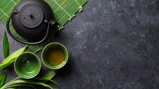 Una tetera y dos vasos con té verde.