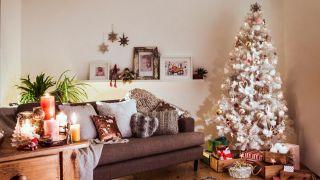 Adornos y bolas plateadas y doradas para un árbol de Navidad blanco