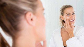Una mujer se aplica una crema, frente al espejo, en el rostro.