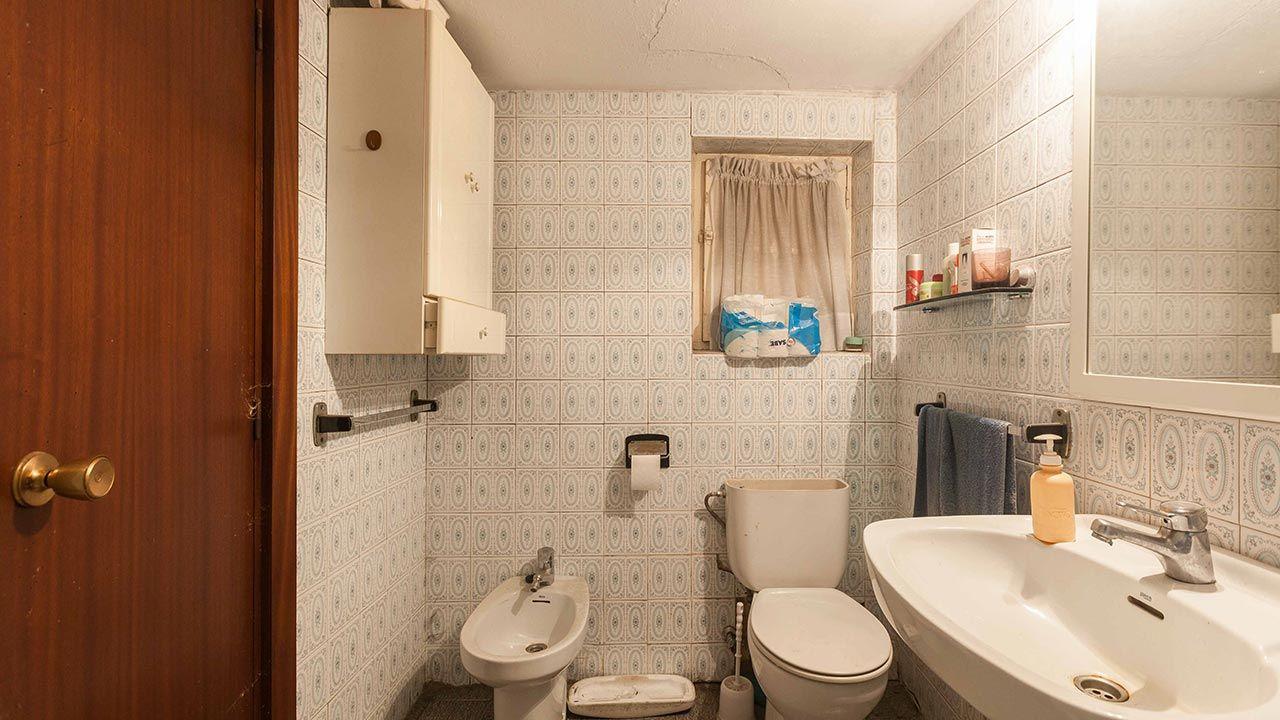 Baño muy pequeño, anticuado y deteriorado