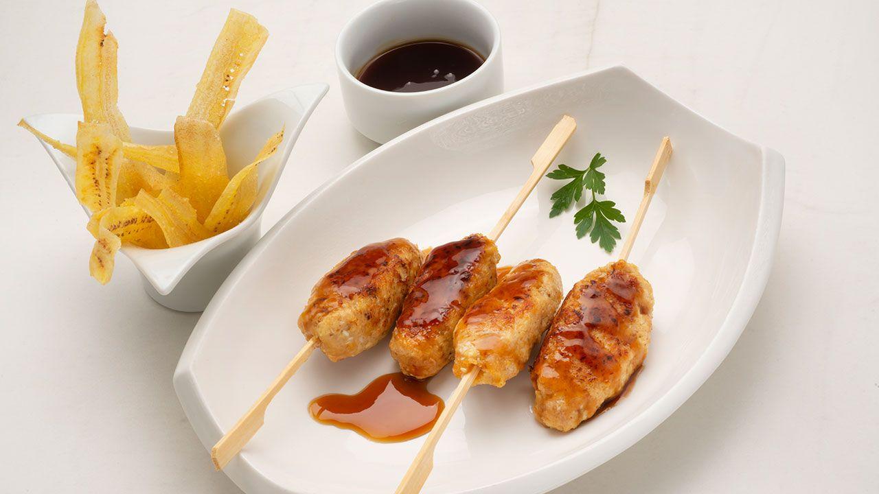 Brochetas de pollo jugosas con salsa teriyaki casera y chips de plátano macho