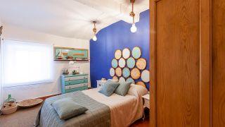 Dormitorio de estilo mediterráneo con cabecero de discos de madera