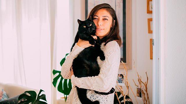 Gato negro abrazado a su dueña