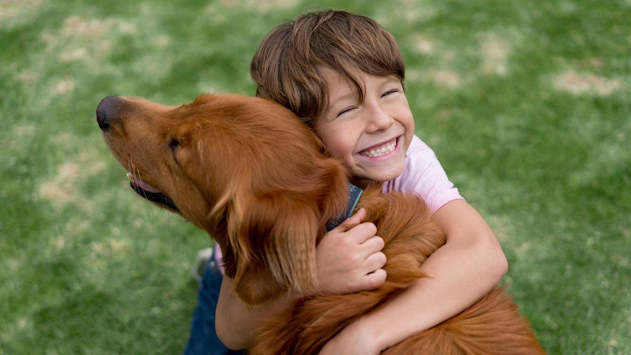 Niño feliz abrazando a su perro