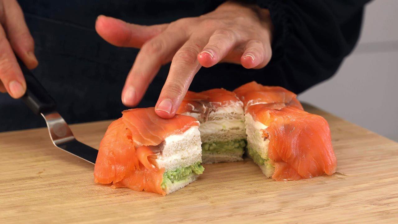 Corte del pastel de salmón con queso crema y aguacate