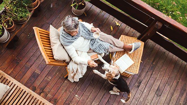Mujer sorda dando un premio al perro señal tras alertarla