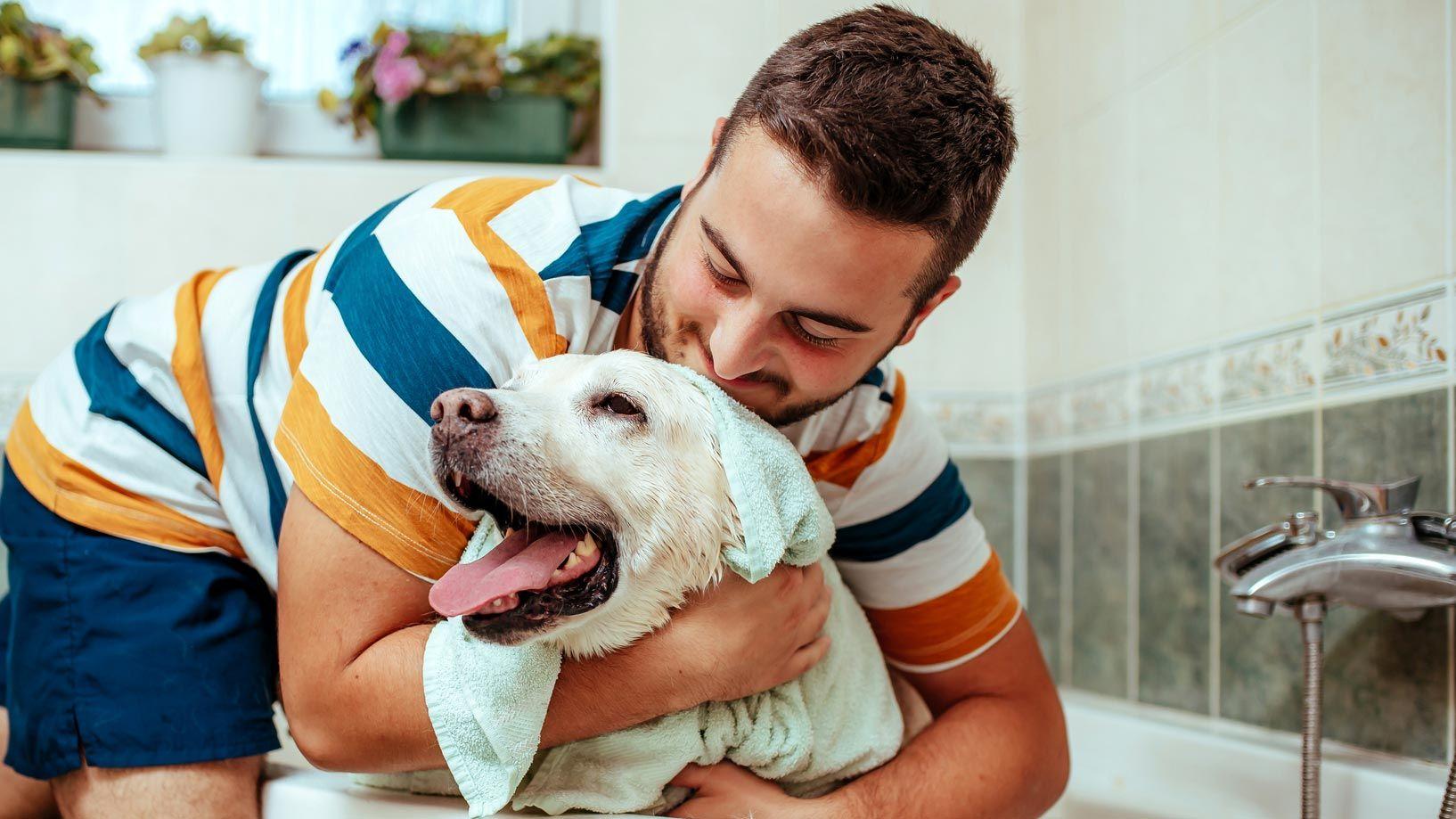 Chico abrazando as su perro tras su baño
