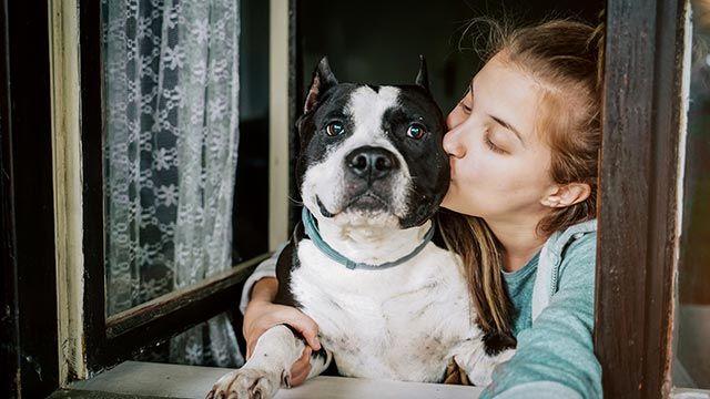Chica dándole un beso a su perro