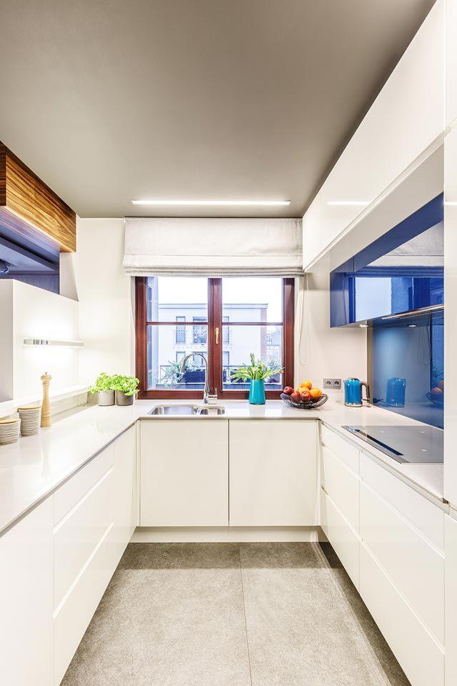 Cocina blanca alargada y estrecha con armarios en azul