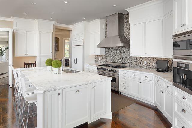 Cocina blanca con detalles en gris y negro y muchos complementos.