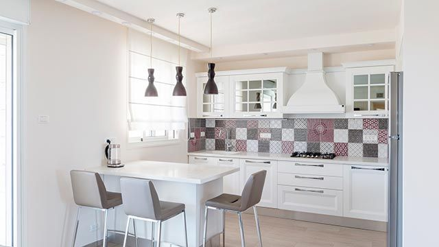 Baldosas hidráulicas de mosaicos en el frontal de una cocina blanca.