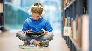 Niño con auriculares escucha música mientras lee un libro en la biblioteca.