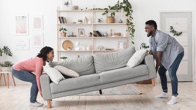 Pareja colocando el sofá en el salón