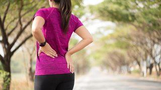Mujer sufre dolor de espalda mientras se ejercita.